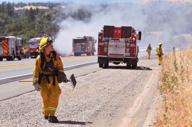 Calfire firefighters survey the hillsides surrounding the motorhome fire on Highway 20 west of Penn Valley Thursday afternoon, ensuring that no wildland spot fires could spread from the vehicle fire.