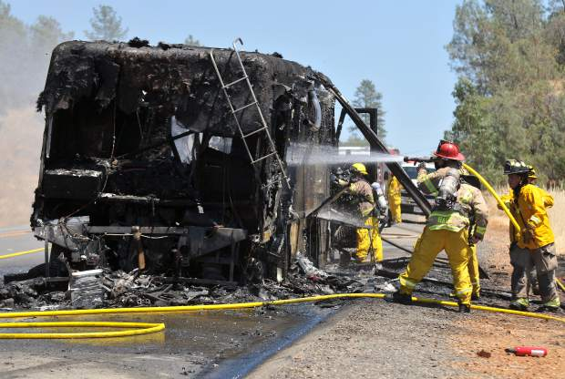 Firefighters douse a coach-style motorhome that caught fire Thursday afternoon on Highway 20 at Poker Flats Road, west of Penn Valley. Crews stayed on scene to monitor the hillsides to make sure that no wildland spot fires could spread from the vehicle fire.