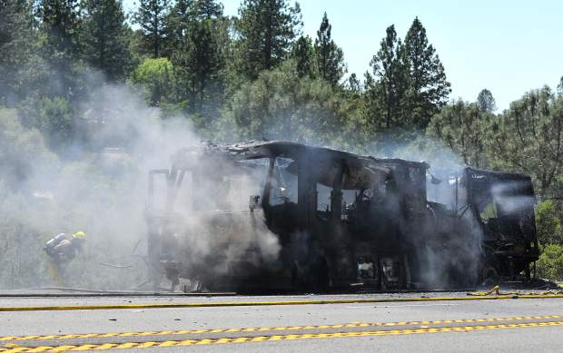 Firefighters douse a coach style motorhome that caught fire Thursday afternoon on Highway 20 at Poker Flats Road, west of Penn Valley. Crews stayed on scene to monitor the hillsides to make sure that no wildland spot fires could spread from the vehicle fire.