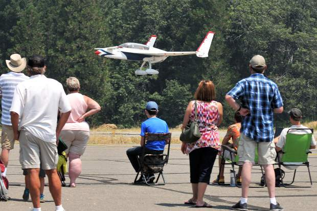 Crowds watch an experimental aircraft do a flyby over the landing strip.