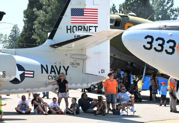 Folks sit in the shade of the airfcraft on display during Saturday's Air Fest.
