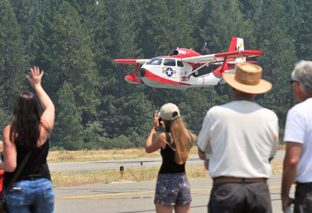 Air Fest goers wave at the passing aircraft.