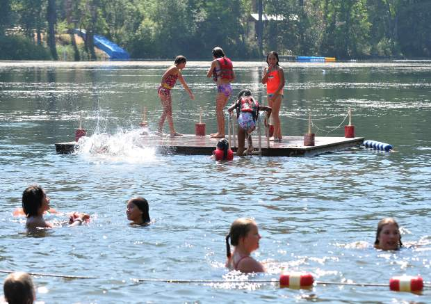 A group of youngsters at Camp Del Oro swim and splash on their side of Lake Vera.