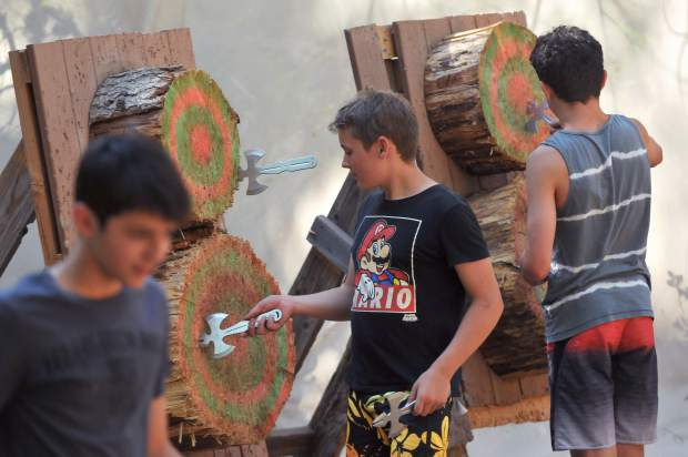 A group of boys pull instruments of medieval destruction from their wooden targets during one of the many activities offered at Camp Augusta in Nevada City.