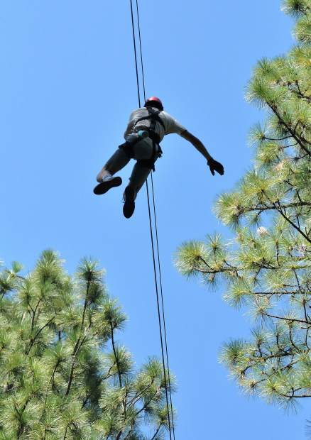 A zipliner travels along the canopy ziipline tour that gives campers at Camp Augusta a two-hour view of the tree tops above Lake Vera.
