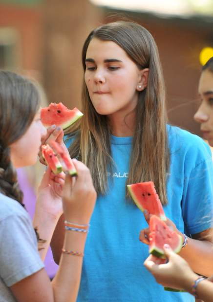 Charlotte Theat of Piedmont California enjoys the daily afternoon serving of watermelon with some of her friends before splitting off to the evening's activities at Camp Augusta.