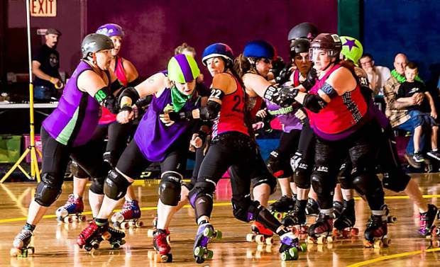 Outlaws blockers hold up an opposing jammer during a roller derby bout.