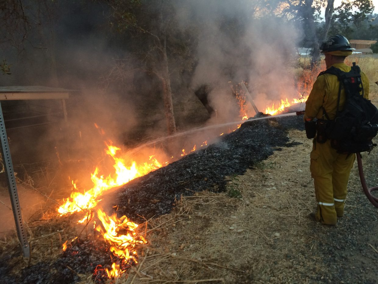 A firefighter attempts to contain a blaze at the Detwiler Fire.