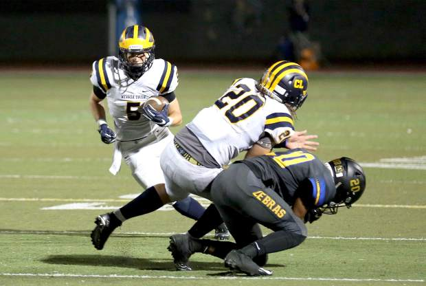 Nevada Union's Tyler Nielson cuts behind a Justin Houlihan block during a game against Lincoln at Lincoln High School Friday night.