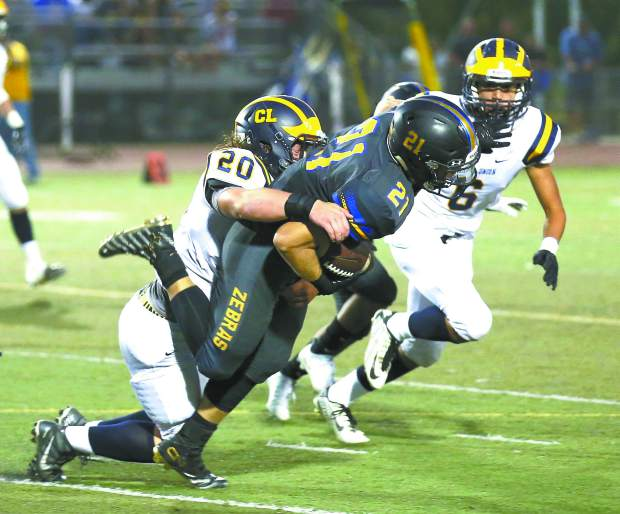 Nevada Union's Justin Houlihan makes a tackle during a game against Lincoln at Lincoln High School Sept. 9.