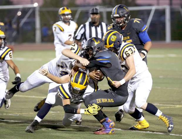 Nevada Union's Will Smith (15), Luke Cornish (63) and Ethan Garrity (74) gang tackle a Lincoln ball carrier during a game against Lincoln at Lincoln High School Friday night. NU won the game 21-14.