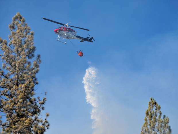 A fire helicopter makes one of many water drops onto the Grizzly Fire which was kept to less than 10 acres Friday evening.
