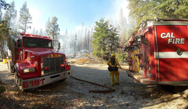 A Cal Fire firefighter tends to the water tenders, making sure that there's enough water for the ground crews to fight the Grizzly Fire Friday afternoon east of North Columbia in rural Nevada County.