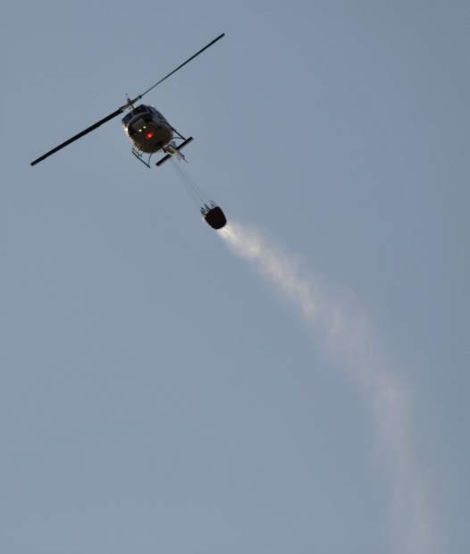 Water sprays from the bucket of a fire helicopter on its way to make a drop on the Grizzly Fire Friday evening east of North Columbia in rural Nevada County.