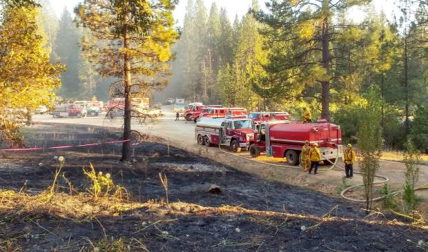 Firefighters assess the scene of Friday's Grizzly Fire, which was kept to under 10 acres due to a heavy ground and air attack.
