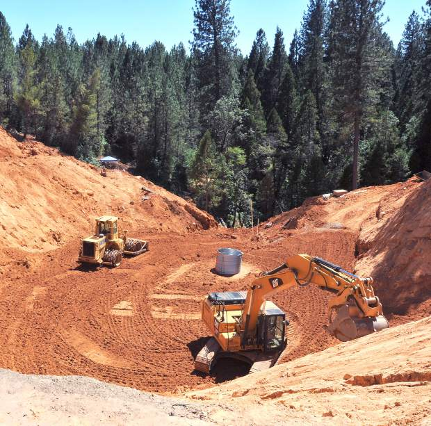 Earth moving equipment sits idle at the scene of the Little Wolf Creek Sinkhole while crews work to line the new culvert (in place underneath) with concrete.