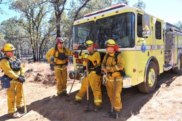 From left, Grass Valley firefighters Anthony Scarafiotti, Captain Robert Bundy, Mike McClain, and Engineer Roque Barrera take a break in front of Cal OES Engine 334 in between mopping up fire lines and putting out hot spots Tuesday at the site of the Wall Fire burning in Butte County.