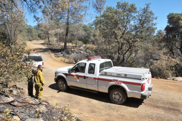 Cal Fire vehicles and personnel occupy a dirt road off of Forbestown Road Tuesday in Butte County where portions of the Wall Fire burned. The firefighters are keeping in contact with the rest of Division H, including Grass Valley's OES 334.
