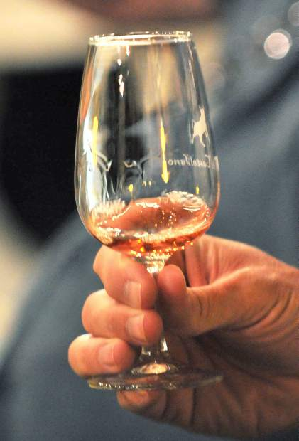 A wine taster examines a glass of wine during Saturday's Wine Tour.