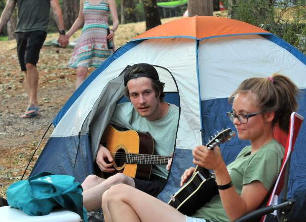 While the music plays on the main stages, Reno's Connor Kirby (left) and Haley McGuire settle into the camping area during their first World Fest weekend.
