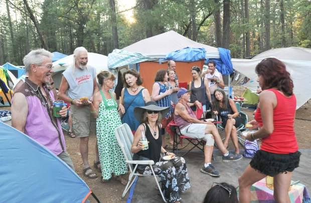 A group of yearly campers celebrate the birthday of Feral Hollowell (center) Friday evening at World Fest in the Nevada County Fairgrounds.