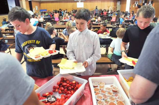 Deer Creek Elementary School fourth graders Cory Fowler (from left), Xander Kloborg-Houser, and Ryan Pack line up to receive their lunch from the new Foothills Fresh lunch program being unveiled at many area schools with the help of Sierra Roots.