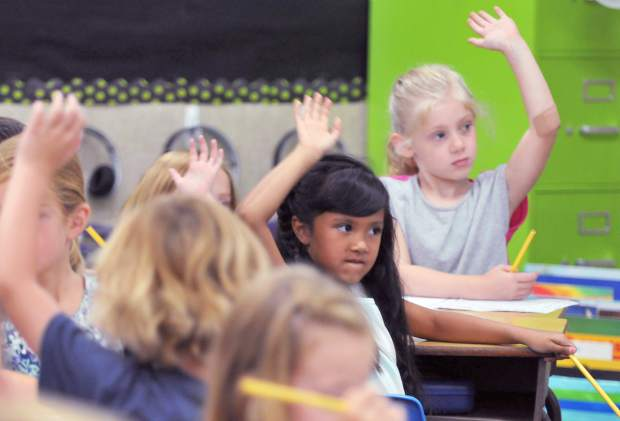 Eager young minds at Deer Creek Elementary School raise their hands to ask a question during the first day of first grade in Nevada City Wednesday.