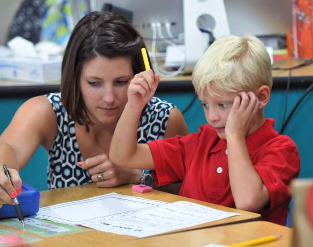 Deer Creek Elementary School first grade teacher Mrs. Russo, helps student Grant Gidlund write his first name on one of his first school assignments.