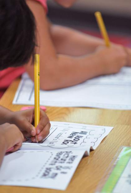 First graders work on their first assignments during their first day of school Wednesday morning at Deer Creek Elementary School in Nevada City.