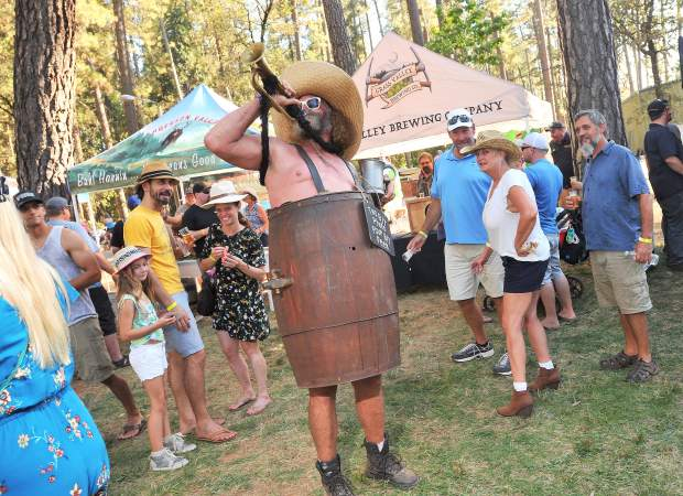 A man in a barrel toots his horn to the delight of festival goers during the 28 annual Sierra Brewfest, benefiting Muisc in the Mountains, Saturday afternoon at the Nevada County Fairgrounds in Grass Valley.