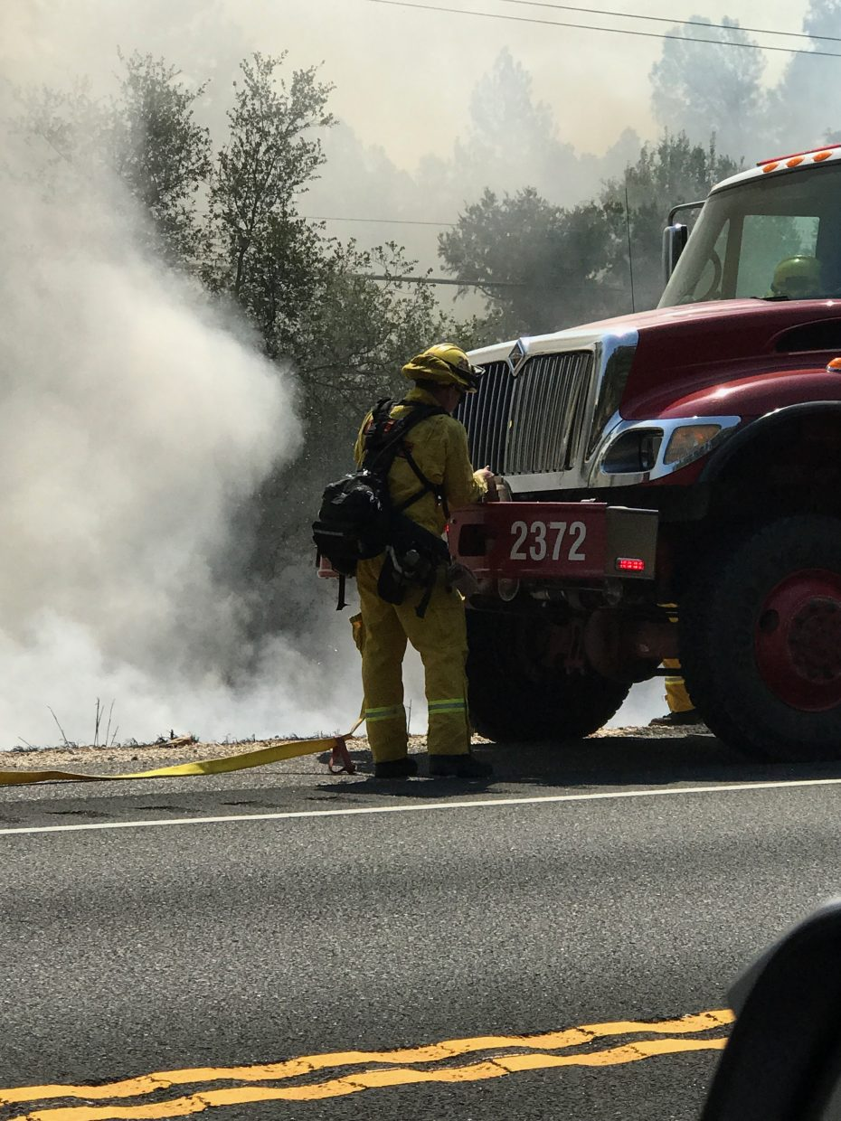 A firefighter and engine at the Carriage Road fire Thursday.