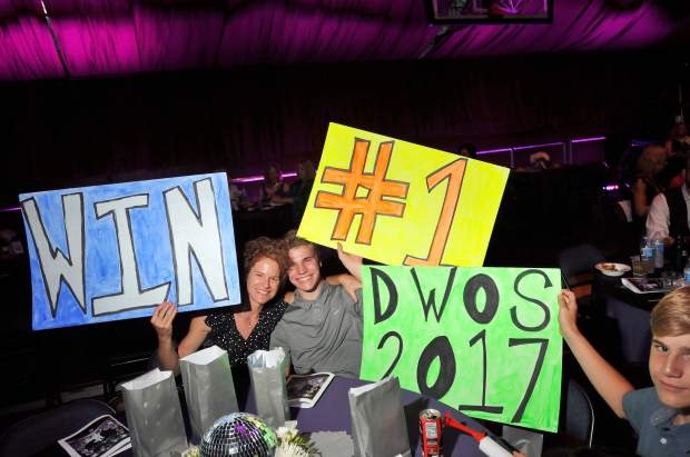Attendees hold signs showing support for their favorite dance competitors.