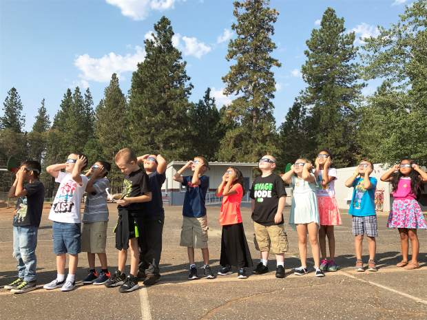Students from Ms. White's second grade class at Scotten School stepped outside to take in the partial eclipse through solar glasses Monday morning. Scotten School classes took turns viewing the eclipse and learning about the mechanics of what caused the rare event.