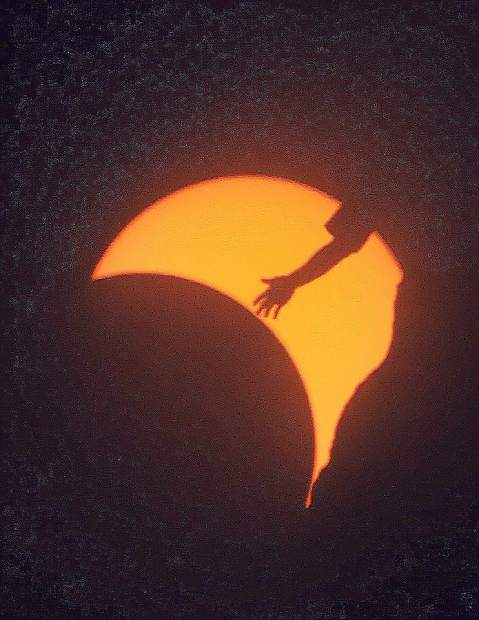 Rock climbers are silhouetted by the partial solar eclipse Monday at Smith Rock State Park in central Oregon.