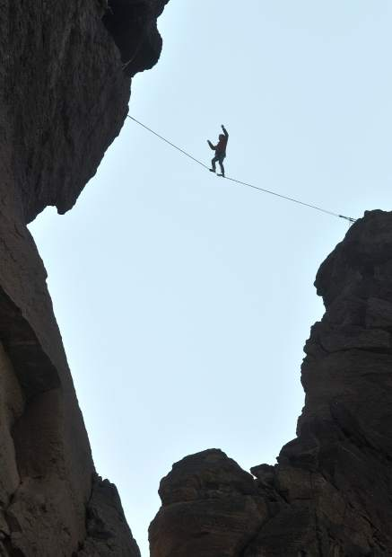 A slack liner gets into position for the full solar eclipse on the Monkey Face rock formation in the Smith Rock State Park in Terrebonne Central Oregon Monday morning.