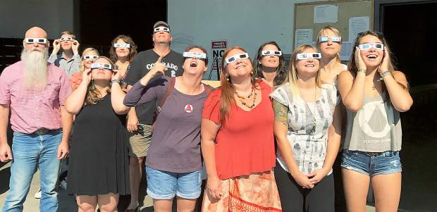 Staff members, and friends, take a break to watch the partial solar eclipse above western Nevada County Monday morning.
