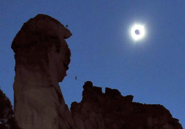 Rock climbers and slack liners bask in the dark of the sun atop the 3,075-foot Monkey Face rock formation at the Smith Rock State Park Monday morning in Terrebonne central Oregon, where eclipse viewers experienced a 100 percent eclipse of the sun for a little over a minute.