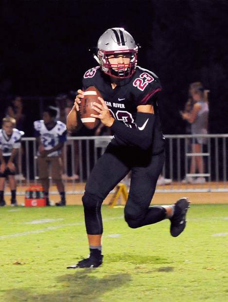 Bear River's Calder Kunde rolls out to pass during a game against Orland Friday. The Bruins topped the Trojans 49-7.