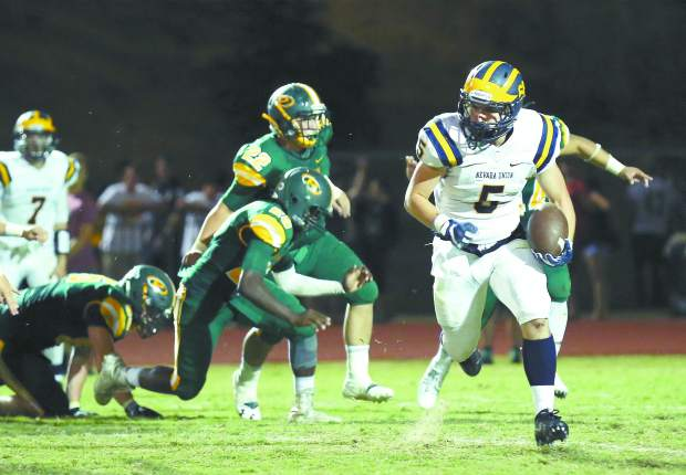 Nevada Union's Tyler Nielson runs the ball during a game against Placer at Le Febvre Stadium Friday night.
