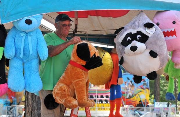 A Brian's Concessions employee hangs stuffed animals at the ring toss game for the 2017 Nevada County Fair.