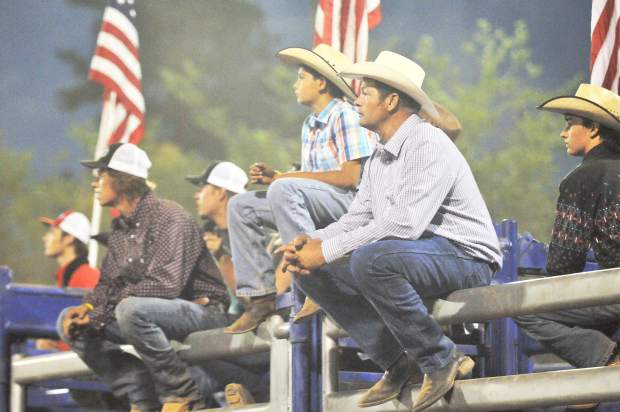 Cowboys take a break on the chutes while watching the flying cowboys do their motorcycle stunt show at the Nevada County Fair arena.