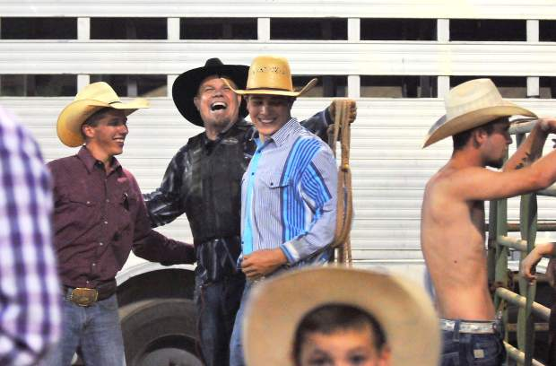 Cowboys share a laugh after the bull riding competition of the Flying U Rodeo Wednesday night of the fair.