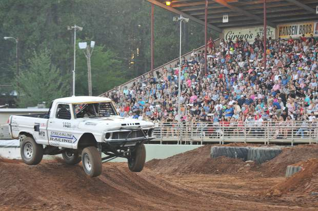 A streamline racing tuff truck gets air as it comes off of a ramp on the course of the Nevada County Fair's Monster Truck and Tuff Truck competition.