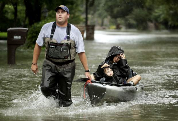 People evacuate a neighborhood in west Houston inundated by floodwaters from Tropical Storm Harvey on Monday, Aug. 28, 2017, in Houston, Texas. (AP Photo/Charlie Riedel)
