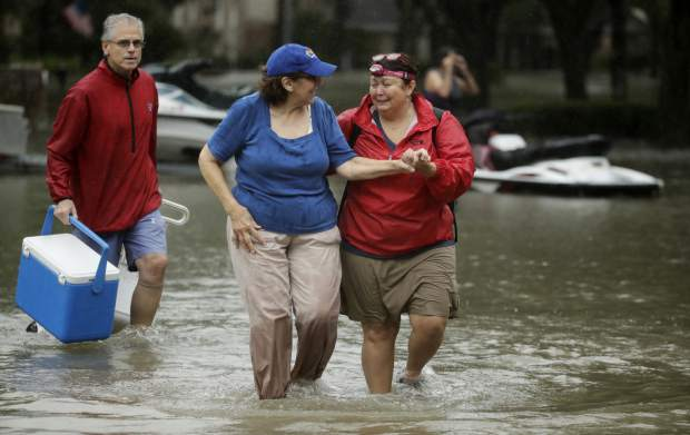 Julie Rios, left, walks out of their flooded neighborhood with newly-met neighbor Gina Delber, right, as they evacuate their homes that are inundated by floodwaters from Tropical Storm Harvey on Monday, Aug. 28, 2017, in Houston, Texas. (AP Photo/Charlie Riedel)