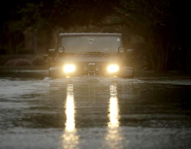A Jeep drives through a neighborhood inundated by floodwaters from Tropical Storm Harvey on Monday, Aug. 28, 2017, in Houston, Texas. (AP Photo/Charlie Riedel)