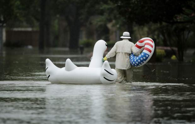 A man walks to his home in a neighborhood inundated by floodwaters from Tropical Storm Harvey on Monday, Aug. 28, 2017, in Houston, Texas. (AP Photo/Charlie Riedel)