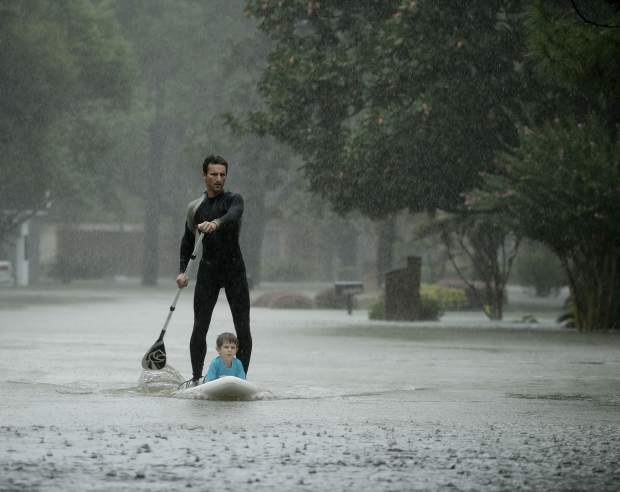 Alexendre Jorge evacuates Ethan Colman, 4, from a neighborhood inundated by floodwaters from Tropical Storm Harvey on Monday, Aug. 28, 2017, in Houston, Texas. (AP Photo/Charlie Riedel)