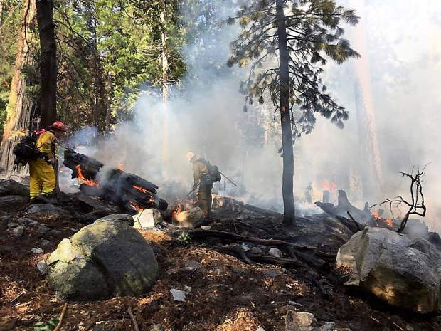 Firefighters work to contain the flames of a 1/4 acre fire near Rucker Lake and Lake Spaulding in the Tahoe National Forest Wednesday afternoon.