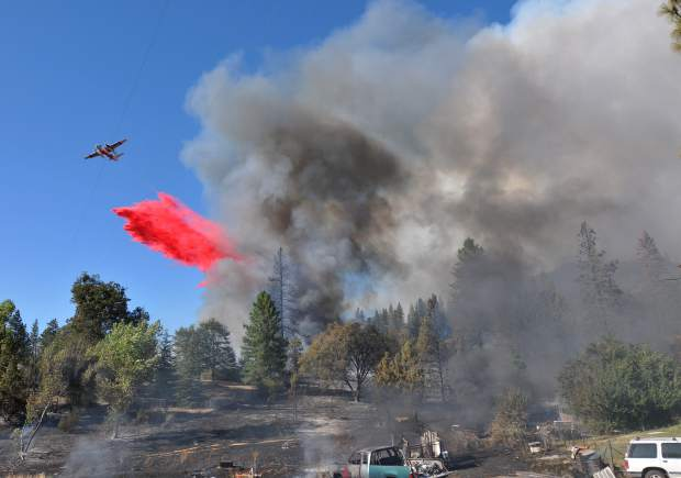 A Cal Fire air tanker drops a load of fire retardant behind Peterson's Corner in attempts to prevent the fire from advancing upon North San Juan Wednesday afternoon. By Wednesday evening, officials were calling for the evacuations of downtown North San Juan and parts of Ananda Village.